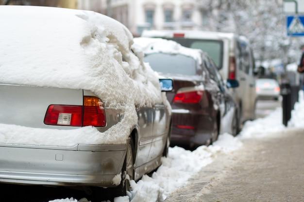 Voitures garées sur un côté de la rue de la ville couverte de neige