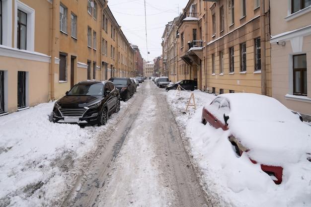 Voitures garées couvertes de neige sur une route enneigée non nettoyée après des chutes de neige. mauvais temps hivernal, augmentation des précipitations et des niveaux de neige.