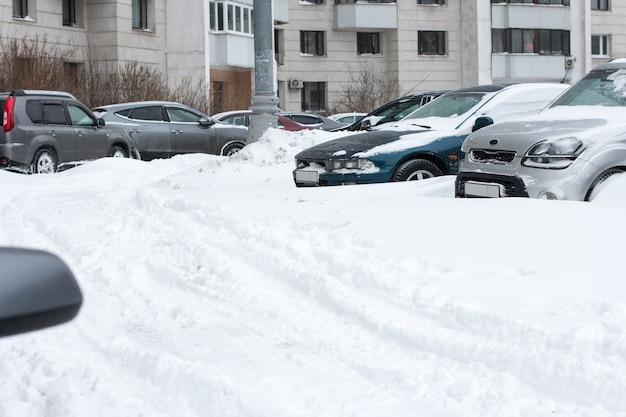 Voitures garées dans la cour en hiver. véhicules couverts de neige lors de fortes chutes de neige.