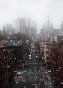 Voitures garées entre les bâtiments sous un ciel nuageux pendant la journée