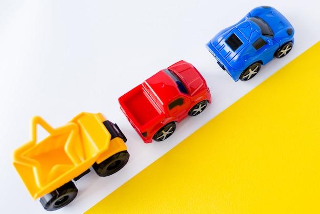 Voitures de jouets pour enfants sur blanc et jaune.