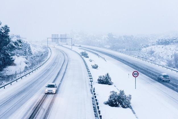 Voitures roulant sur une route enneigée.