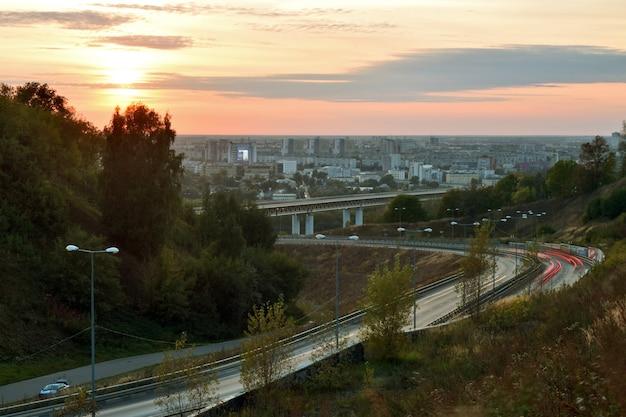 Les voitures se déplacent à nijni novgorod au coucher du soleil