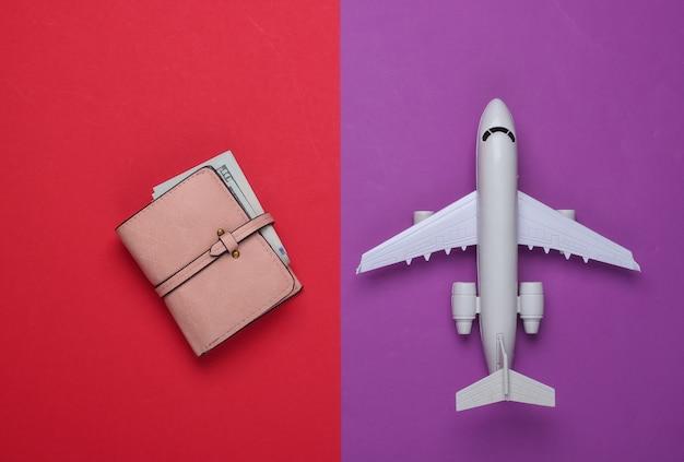 Vol aérien, concept de voyage. avion jouet, portefeuille avec de l'argent sur un rouge-violet