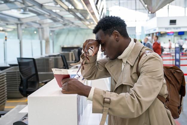 Vol d'annulation de l'homme, a raté l'avion, tient la carte d'embarquement, debout au comptoir d'enregistrement