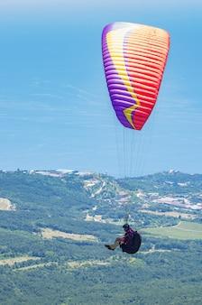 Vol d'un athlète de parapente au-dessus de la côte de la mer dans la région du mont aipetri