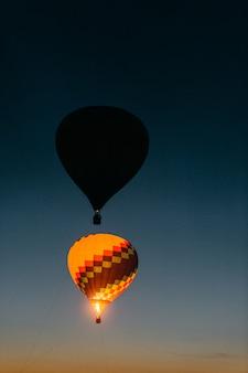 Vol de ballons rougeoyants et clignotants avec des gens haut dans le ciel dans la nuit.