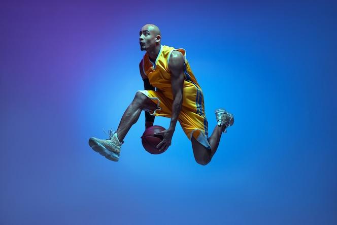 Vol. beau joueur de basket-ball masculin afro-américain en mouvement et action à la lumière du néon sur le mur bleu.