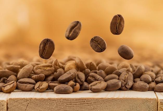 Vol de grains de café frais sur fond flou jaune avec espace de copie. grains de café tombant