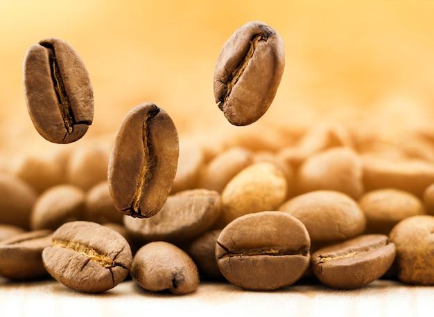 Vol de grains de café frais sur fond flou jaune avec espace de copie.