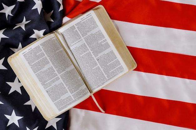 Volant de drapeau américain avec open est en train de lire le livre de la sainte bible avec la prière pour l'amérique sur le drapeau américain