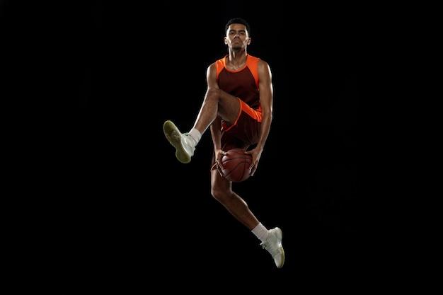 En volant. jeune joueur de basket-ball afro-américain déterminé, s'entraînant en action, mouvement isolé sur fond noir. concept de sport, mouvement, énergie et mode de vie sain et dynamique.
