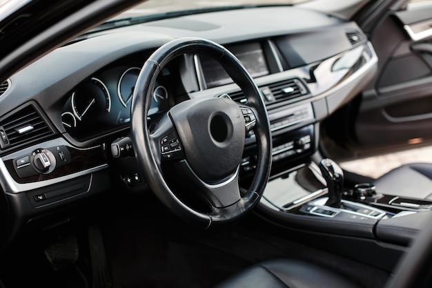Volant, sièges en cuir noir, levier de vitesses et tableau de bord.