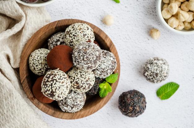 Volants de dattes, noix, noisettes et cacao dans un bol en bois sur une table lumineuse