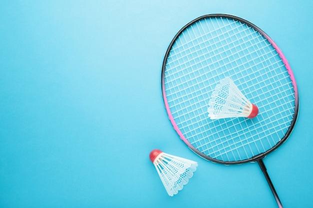 Volants et raquette de badminton sur bleu.
