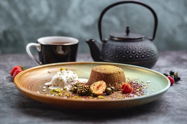 Volcan chocolat teinté doré servi avec glace vanille et baies et thé