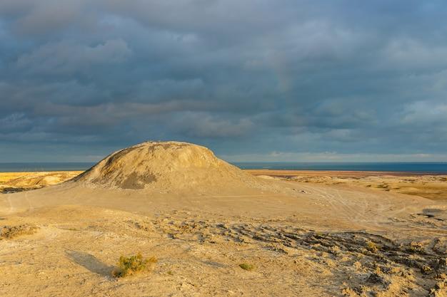 Volcans de boue de gobustan près de bakou, azerbaïdjan. montagne de boue et ciel orageux