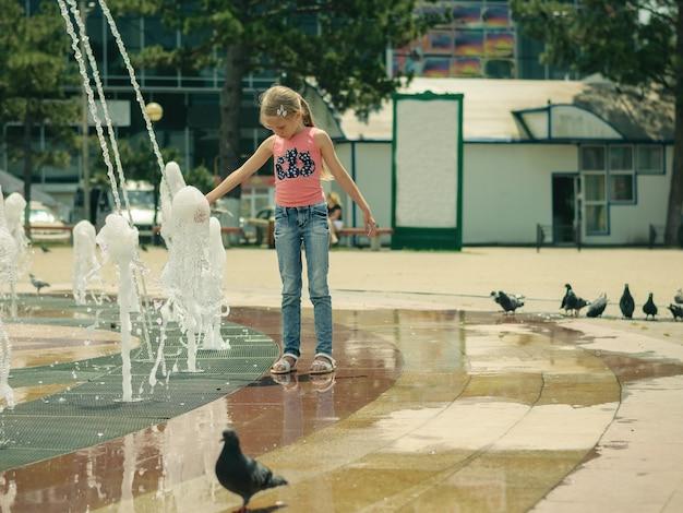 Une volée de pigeons traînant autour des filles dans la fontaine de la ville.