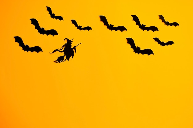 Voler des chauves-souris noires et sorcière sur un balai. décorations en papier halloween sur fond orange