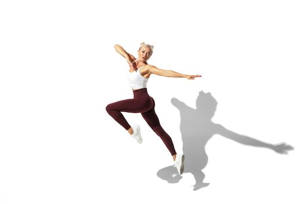 Voler comme un papillon belle jeune athlète féminine pratiquant sur le mur blanc du studio