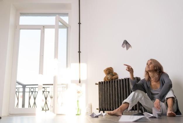 Voler, une femme âgée est assise sur le sol de son appartement et lance un avion en papier avec une expression indifférente