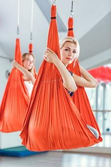 Voler le yoga. deux femmes pratiquent le yoga anti-gravité avec un hamac.