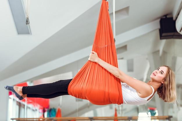 Voler le yoga. une jeune femme pratique le yoga anti-gravité avec un hamac.