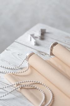 Les volets beiges roulés sont sur une surface en bois.