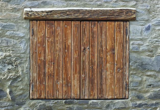 Volets en bois fermés sur une façade en pierre d'un chalet de montagne