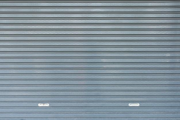 Les volets métalliques enroulent le fond de texture de porte.