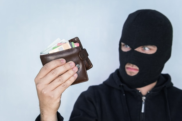 Le voleur en cagoule compte l'argent dans le portefeuille volé. voleur en masque noir tenant un portefeuille et regardant la caméra.