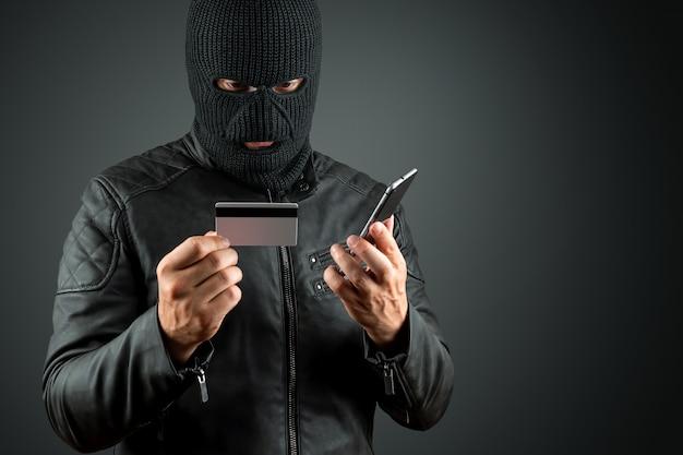 Un voleur en cagoule tient une carte de crédit dans ses mains sur un fond sombre