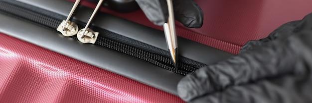 Le voleur avec des gants essaie d'ouvrir la valise avec la poignée