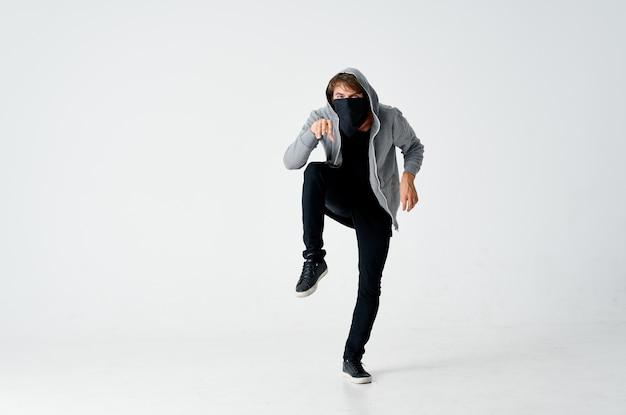 Voleur masculin dans la hotte masque caché sur la pointe des pieds fonds isolé