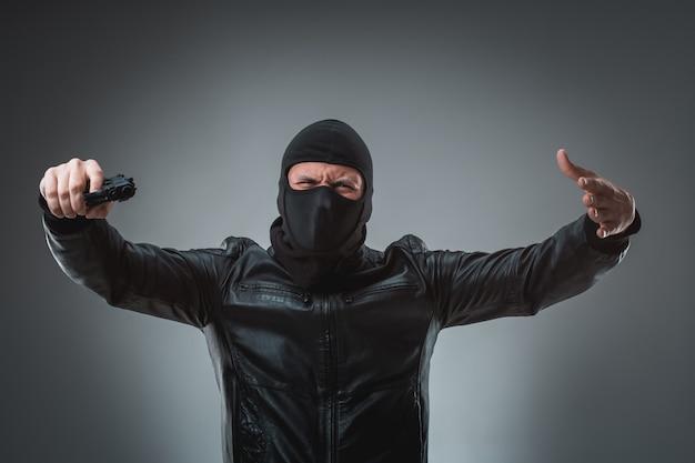 Voleur masqué avec arme à feu, regardant dans la caméra.