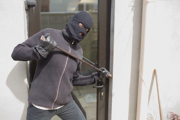 Voleur pénétrer dans la maison en utilisant la barre de corbeau