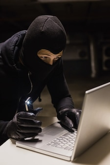Voleur piratant un ordinateur portable tout en faisant la lumière avec son téléphone sur fond noir
