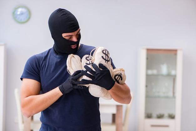 Un voleur portant une cagoule vole des objets de valeur