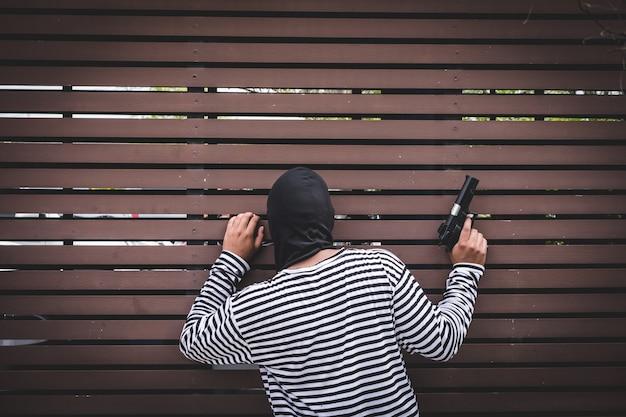 Voleur se cachant derrière le mur