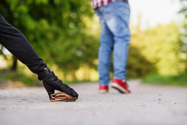 Le voleur en tenue noire soulève un portefeuille avec de l'argent du sol. vol à la tire dans la rue pendant la journée.