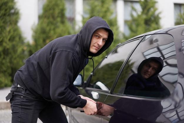 Un voleur de voiture vole une voiture qui casse la porte d'un cambrioleur d'emplois criminels