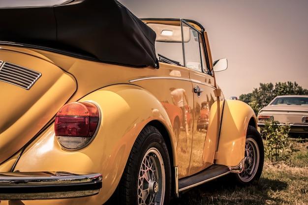 Volkswagen coccinelle cabriolet entièrement restaurée jaune, garée sur l'herbe dans une campagne typiquement italienne. photos avec un très joli cadrage et utilisable comme fond d'écran.