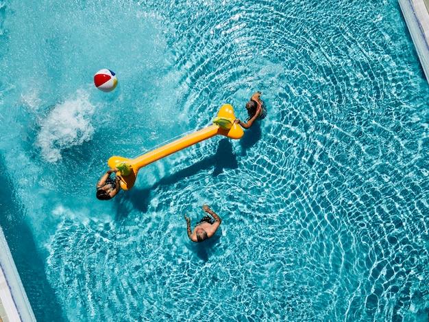 Volley-ball dans la piscine avec deux couples seniors d'amis ou en famille en vacances actives