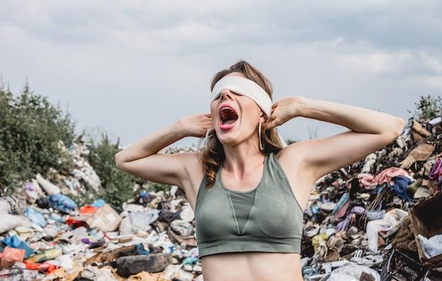 Une volontaire aux yeux bandés hurle d'impuissance dans une décharge de déchets plastiques.