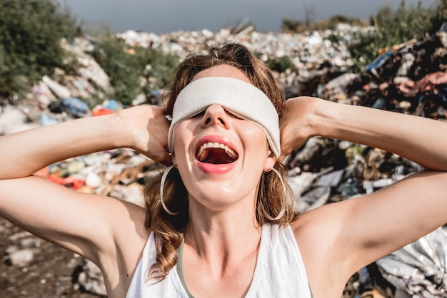 Une volontaire aux yeux bandés hurle d'impuissance dans une décharge de plastique