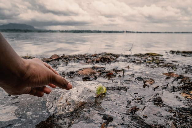 Le volontaire ramassant une bouteille de plastique dans la rivière