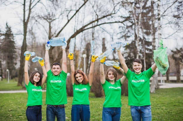 Volontaires élevant des bouteilles en plastique