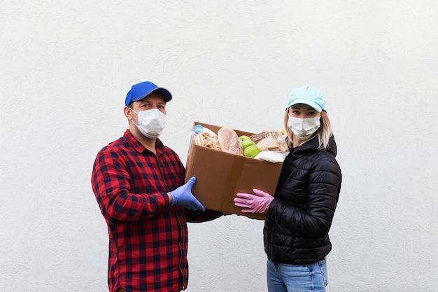 Les volontaires en masques de protection avec une boîte de nourriture