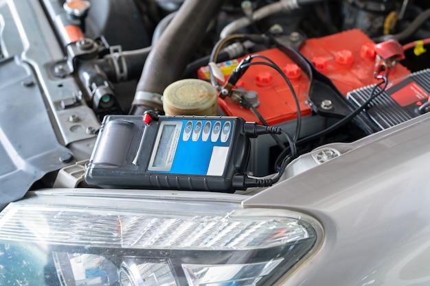 Voltmètre testeur de capacité de batterie pour maintenance dans une automobile d'usine.