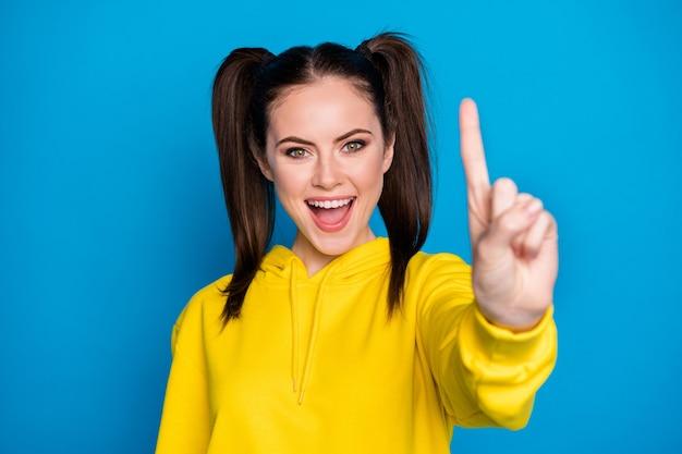 À vos marques, prêt? partez. photo d'une jolie dame à deux queues levant le bras montrant un index bonne humeur ensemble de comptage commencer à porter un pull à capuche jaune décontracté isolé sur fond de couleur bleu vif